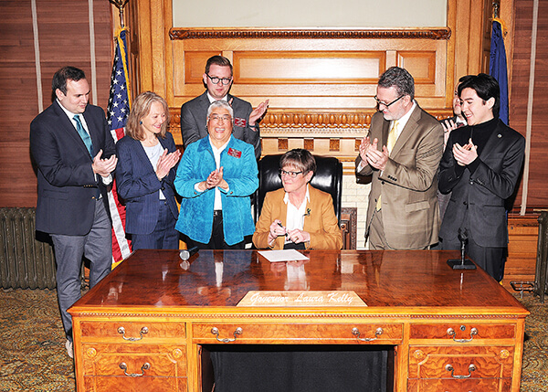 Governor Kelly signs executive order at desk